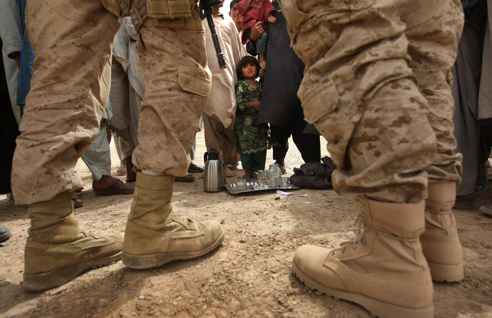 A U.S. counter-intelligence Marine and his translator meet with local Afghan villagers on March 23, 2009 in Kirta, in remote southwest Afghanistan. (John Moore/Getty Images) #