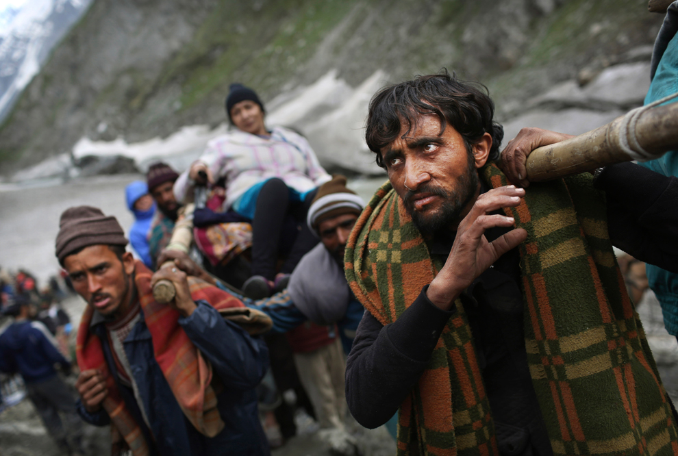 Kashmiri laborers carry a Indian Hindu pilgrim on a trail during the traditional journey to the Amarnath cave, June 28, 2012. Thousands of pilgrims annually go to the remote Himalayan shrine of Amarnath at 3,888 m (12,756 ft) above sea level to worship an icy stalagmite representing Shiva, the Hindu god of destruction. (Kevin Frayer/Associated Press
