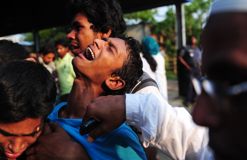 A youth reacts after seeing his relatives bodies, April 24, 2013. An eight-story building containing several garment factories collapsed in Bangladesh, and further highlighted documented safety problems in the clothing industry. Armed with concrete cutters and cranes, hundreds of fire service and army rescue workers struggled to find survivors in the mountain of concrete and mangled steel.(Munir uz Zaman/AFP/Getty Images)