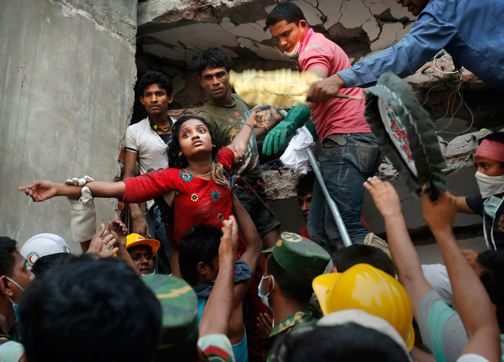 A Bangladeshi woman is lifted out of the rubble by rescuers at the site of a building that collapsed, April 25, 2013. (Kevin Frayer/Associated Press)