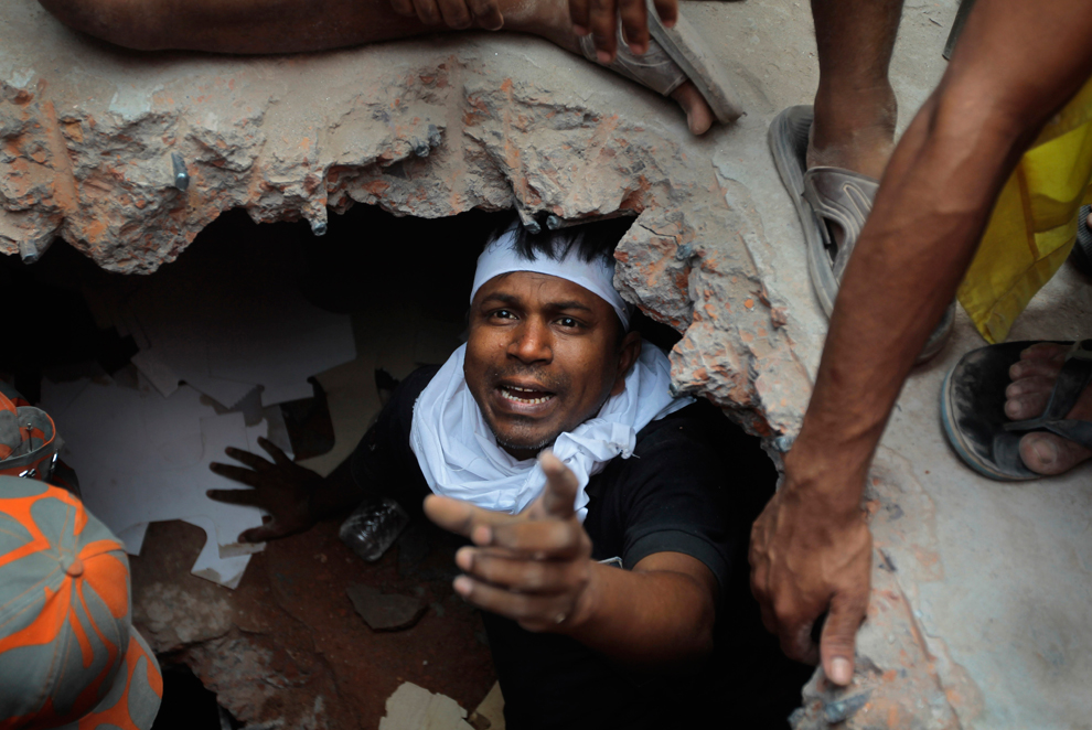 A Bangladeshi rescuer looking for survivors gestures from beneath a concrete slab, April 25, 2013. (A.M.Ahad/Associated Press)