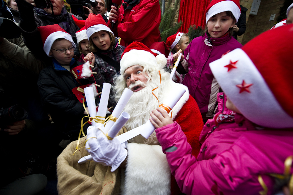 electronic santa claus target. A man dressed as Santa Claus is surrounded by local children giving him