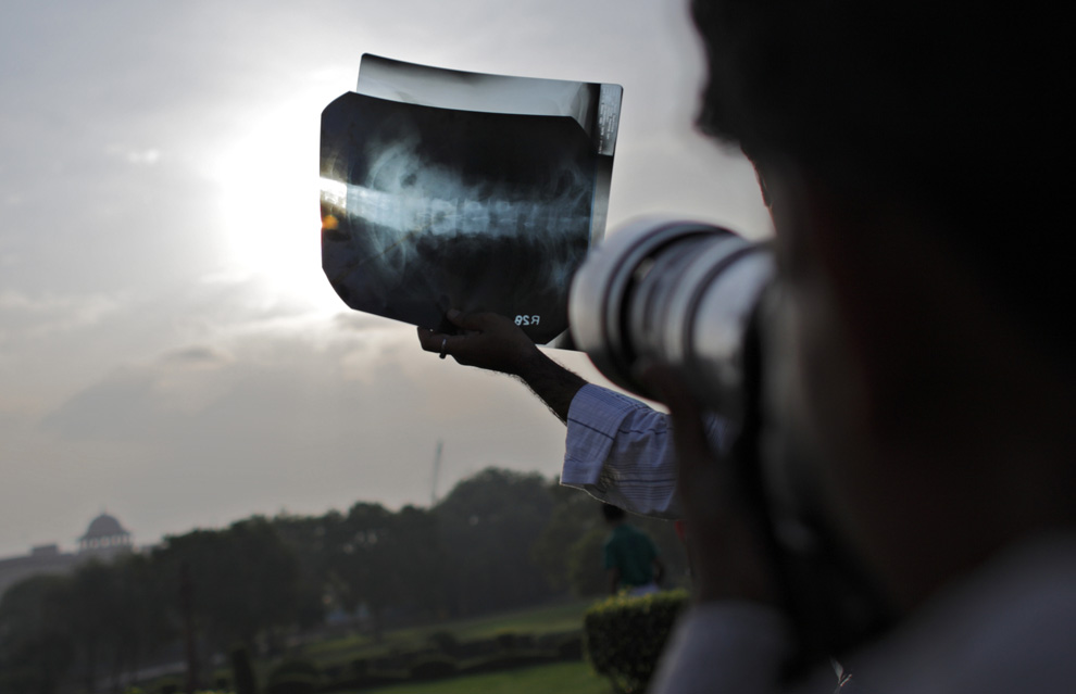 A photographer takes pictures of a solar eclipse through exposed X-ray film during sunrise in New Delhi on July 22, 2009. (TENGKU BAHAR/AFP/Getty Images)