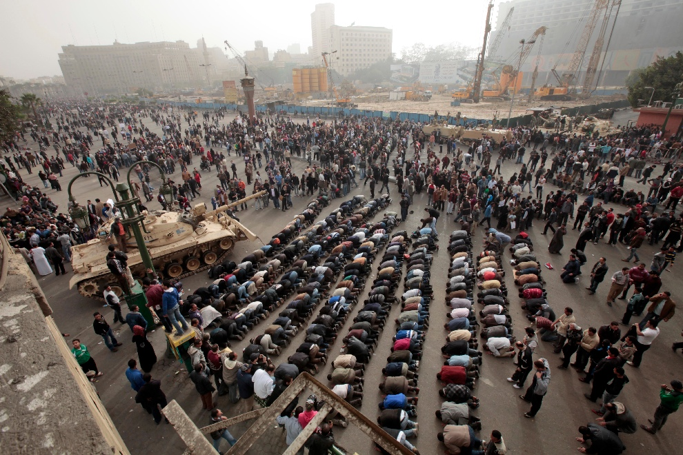 Protesters pray in front of an Egyptian army tank in Liberation Square in Cairo Saturday, Jan. 29. In several parts of the city, confrontation gave way to camaraderie as protesters and soldiers shared water bottles and stories. (Lefteris Pitarakis/Associated Press)