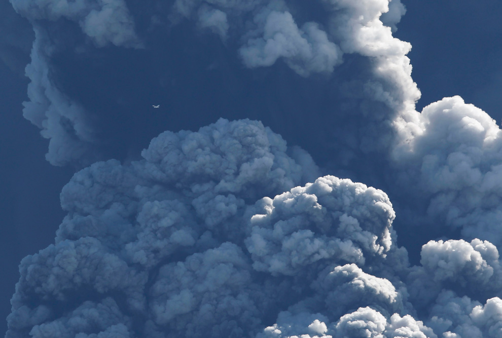 A small plane (upper left) flies past smoke and ash billowing from a volcano in Eyjafjallajokul, Iceland on April 17, 2010 (Photo: REUTERS/Lucas Jackson)