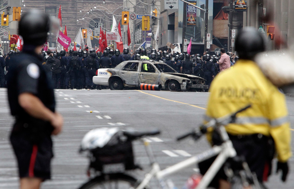 Police officers stand behind their bicycles as protesters are stopped by a line of officers behind a burnt police car during G20 Summit protests in downtown Toronto June 26, 2010. (REUTERS/ Mike Cassese) #