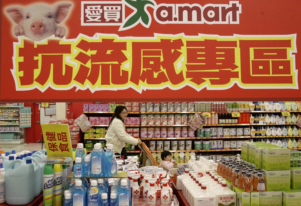 Покупатели проходят мимо отдела супермаркета, в котором продаются средства от гриппа. Тайпей, Тайвань, 4 мая 2009. Вывеска в верхней части фото гласит: «Товары Анти-Грипп». (REUTERS/Pichi Chuang)
