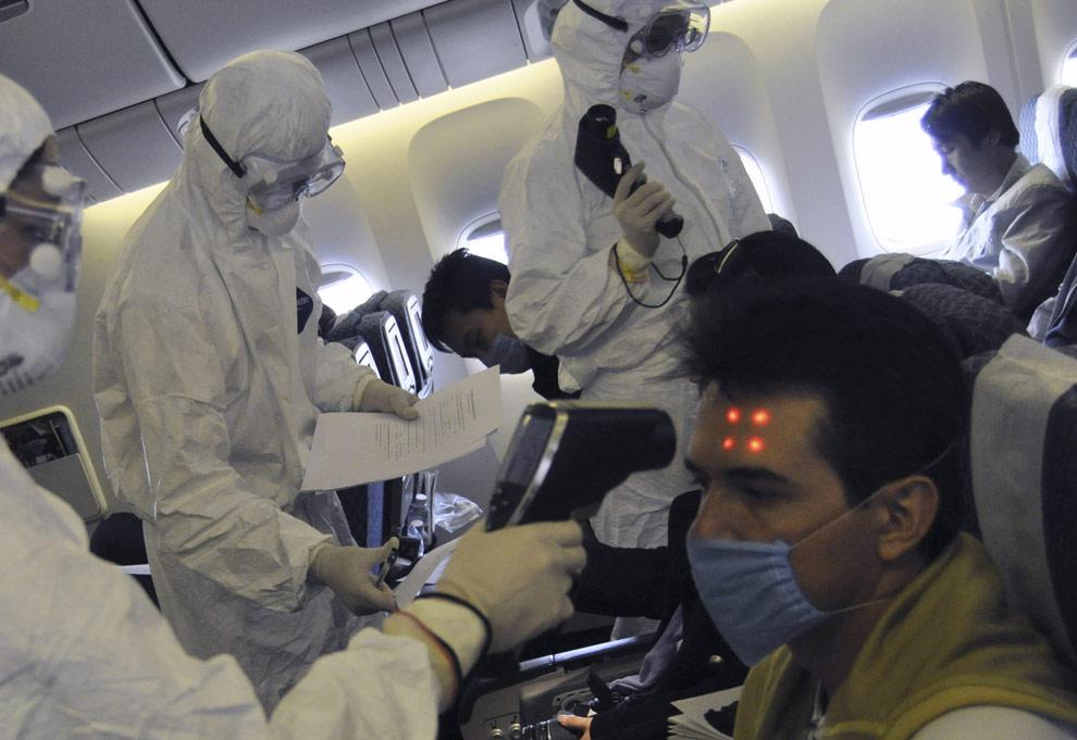 Китайские медработники в защитных костюмах осматривают пассажиров на борту самолета Aeromexico рейс 098 полета AM 98, который приземлился в международном аэропорту Пудун в Шанхае в четверг, 30 апреля 2009. 2 мая, после того как подтвердилась информация о заражении человека, вернувшегося в Китай из Мексики, Пекин отменил рейсы из Мексики в Шанхай. Все пассажиры, летевшие тем рейсом авиакомпании Aeromexico, помещены в карантин. 71 мексиканский гражданин находится в изоляции в гостинице. (AP Photo/EyePress)