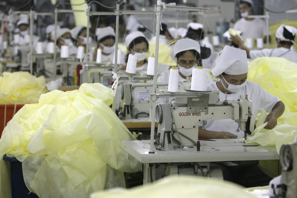 Работники шьют защитные халаты на заводе Medtecs в провинции Батаан, расположенной к северу от Манилы. 30 апреля 2009. Завод Medtecs на Филиппинах производит защитные маски и халаты. С началом вспышки свиного гриппа спрос на продукцию завода вырос в три раза. (REUTERS/ Romeo Ranoco)