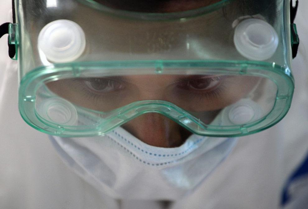 Медицинский работник в специальной защитной маске в военно-морском госпитале Мехико, где проходит обследование людей с симптомами свиного гриппа. 29 апреля 2009. (AP Photo/Enric Marti)