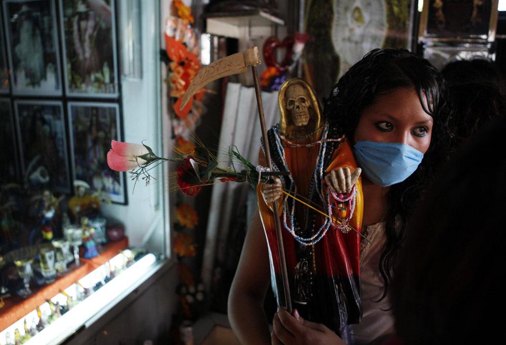 Мексиканка в защитной маске с фигуркой-скелетом, изображающей мексиканскую народную святую, известную как Santa Muerte или Святая Смерть, во время церемонии в Мехико, в пятницу 1 мая 2009. (AP Photo/Eduardo Verdugo)