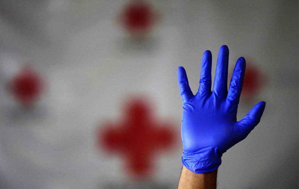 Работник Красного Креста во время учебных занятий с волонтерами показывает, как правильно надевать и снимать защитные перчатки. Гватемала, 29 апреля 2009. (REUTERS/ Daniel LeClair)