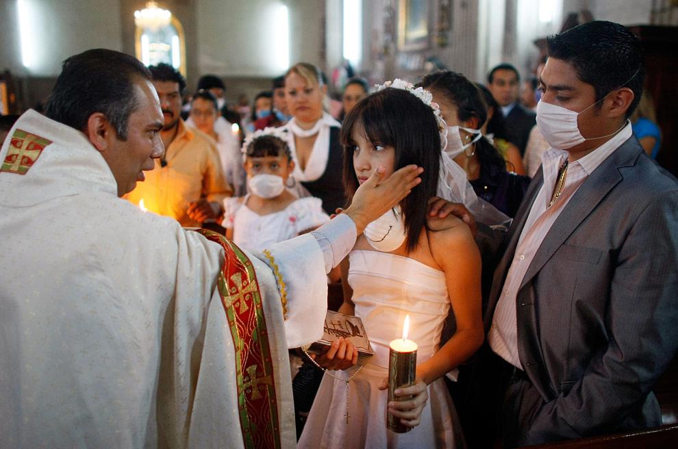 Священник Рохелио Гомес Перальта молится за Джейми Ксимену во время церемонии крещения в церкви 3 мая 2009 года в Мехико. (Joe Raedle/Getty Images)