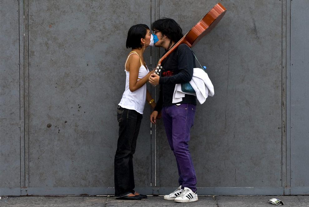 Парень и девушка в защитных масках целуются в Мехико на площади Zocalo 30 апреля 2009. (LUIS ACOSTA/AFP/Getty Images)