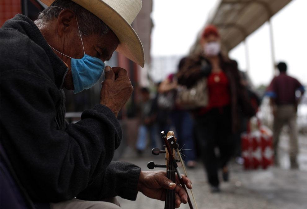 Уличный музыкант Маргарито Гарсия, сидит у железнодорожного перехода Сан Исидро в Тихуане, Мексика 1 мая 2009. (AP Photo/ Guillermo Arias)