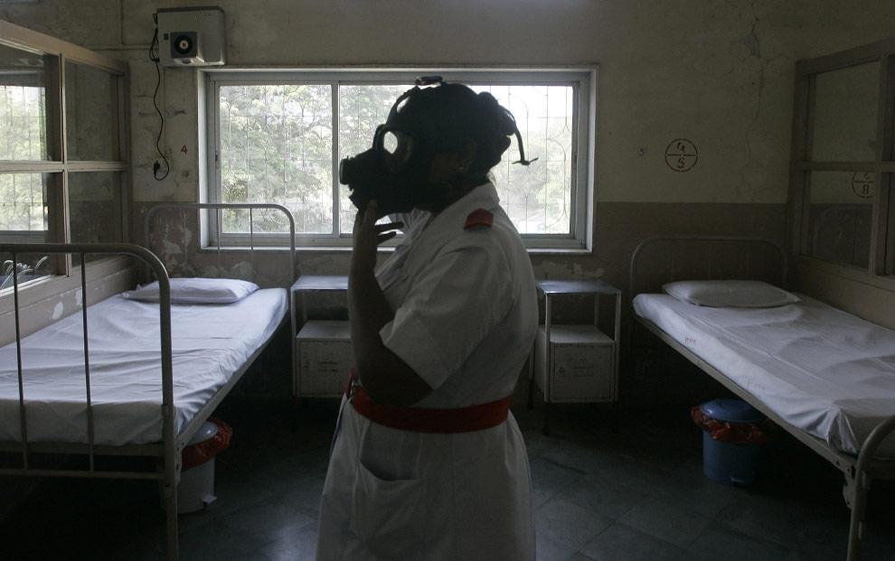 Медсестра демонстрирует, как надевать высокоэффективный сухой воздушный фильтр (HEPA) в специальной палате во время подготовки к возможной вспышке свиного гриппа в больнице Мумбая, Индия в воскресенье, 3 мая 2009. (AP Photo/Rajanish Kakade)
