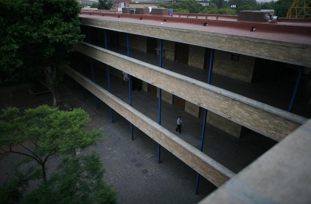 Женщина идет по пустому зданию Национального независимого университета Мексики, UNAM в Мехико, в понедельник, 4 мая 2009. На этой неделе планируется снова открыть школы, предприятия, музеи и библиотеки закрыты из-за вспышки свиного гриппа. (AP Photo/Miguel Tovar)