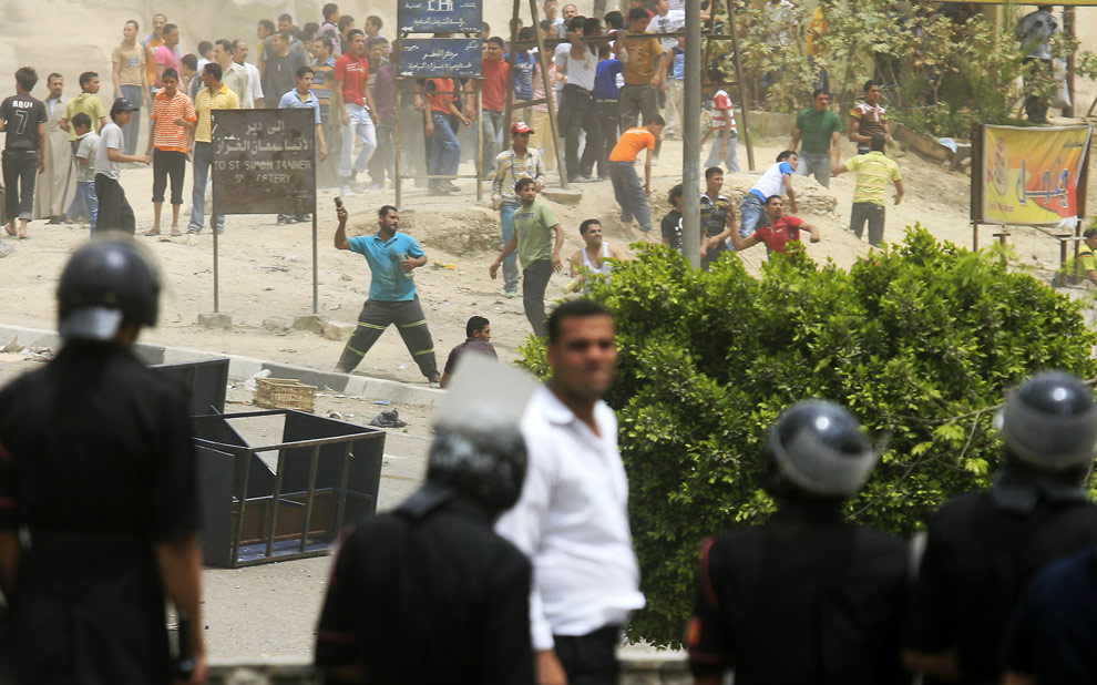 Египетские фермеры кидают камни в полицейских во время протеста против массового убоя свиней в квартале Аль-Мукатам 3 мая 2009 в Каире. В Египте  свиней разводят исключительно христиане-копты. Они выступили против политики правительства по истреблению всего поголовья свиней в стране ради предотвращения эпидемии свиного гриппа. От 300 до 400 жителей одного из районов Каира, в основном — молодежь, закидали полицейских камнями и бутылками. (KHALED DESOUKI/AFP/Getty Images)