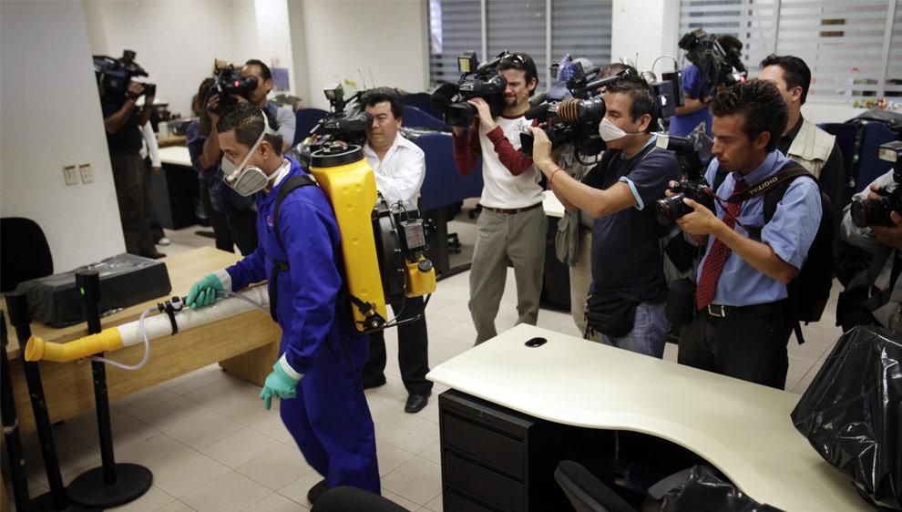 Мужчина разбрызгивает дезинфицирующее средство в классе с целью профилактики свиного гриппа, в то время как представители средств массовой информации наблюдают за ним. Национального независимого университета Мексики, UNAM в Мехико во вторник, 5 мая 2009. (AP Photo/Rodrigo Abd)