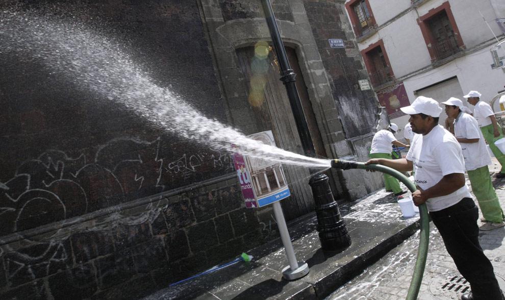 Муниципальные работники моют здания в центре Мехико 5 мая 2009. (REUTERS/Daniel Aguilar)