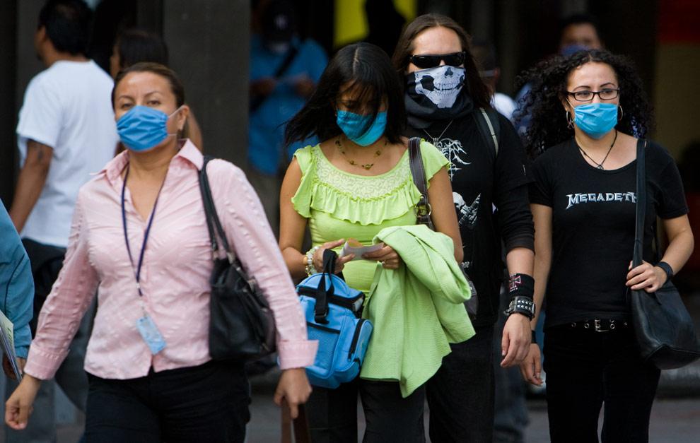 Жители Мехико в масках возвращаются на работу 28 апреля 2009. (OMAR TORRES/AFP/Getty Images)