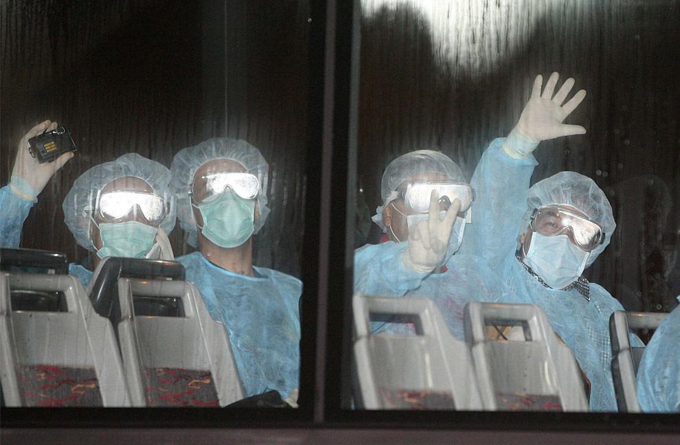 Группа мексиканцев ждет автобус перед началом посадки на самолет в Гонконге рано утром 6 мая 2009. Десятки мексиканцев, которых подвергли изоляции в Китае, вернулись на родину. Заболевших среди них нет. Китайские власти задержали мексиканцев после того, как в самолете, летевшем в Гонконг, был обнаружен пассажир с признаками свиного гриппа. (REUTERS/Mike Clarke/Pool)