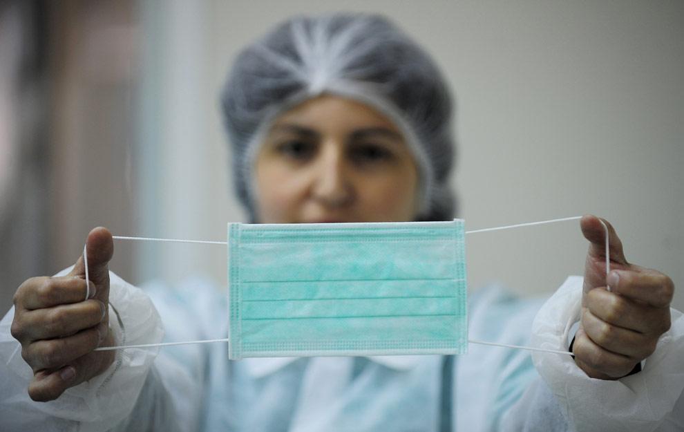 Работница держит защитную маску. Завод медицинских изделий в Cornella de Llobregat, близ Барселоны, Испания. Четверг, 30 апреля 2009. Из-за угрозы свиного гриппа продажи масок выросли с 250 тысяч до 1 млн. единиц в неделю. (AP Photo/Manu Fernandez)
