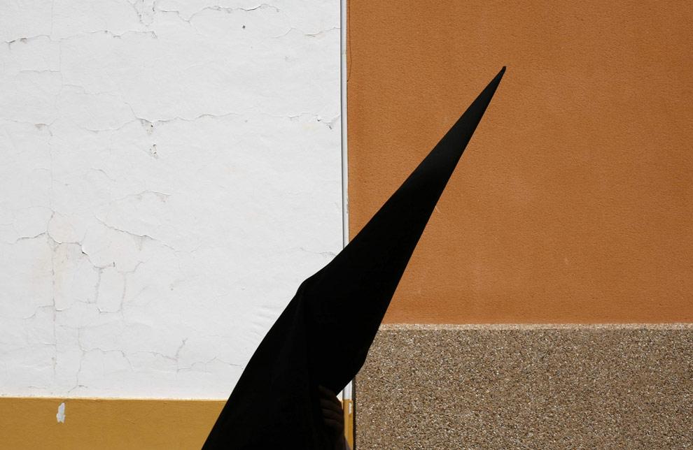 Кающийся грешник в традиционном капюшоне принимает участие в шествие братства  Santa Genoveva в честь Страстной недели в андалузском городе Севилья, на юге Испании, 6 апреля 2009. (REUTERS/Marcelo del Pozo)