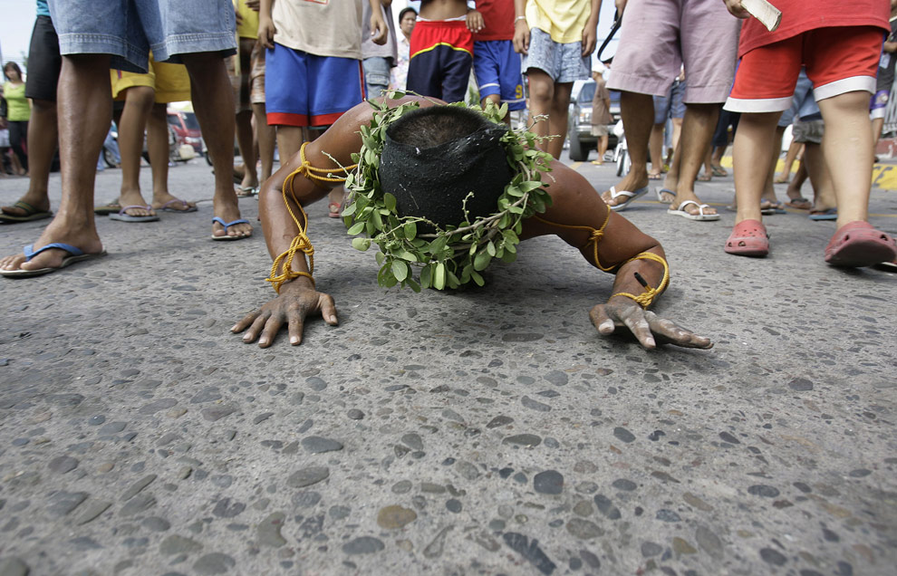 Филиппинской верующий ползет по раскаленной мостовой во время обряда искупления грехов в Сан-Фернандо, в провинции Пампанга на севере Филиппин. Великий четверг, 9 апреля 2009. (AP Photo/Aaron Favila)