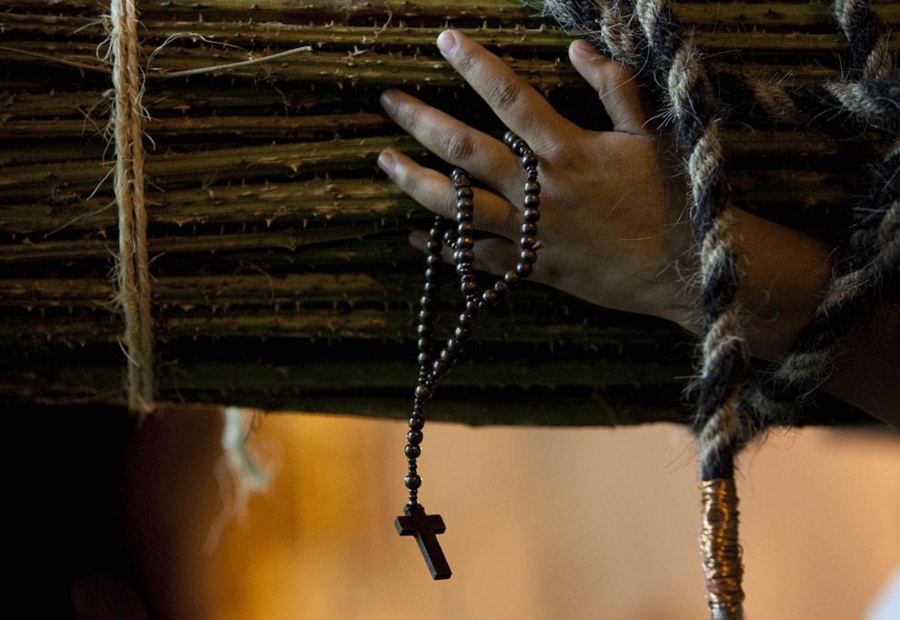 Верующий с вязанкой кактусов на плечах, которую он несет в качестве покаяние, во время процессии кающихся грешников в мексиканском городе Таско, 9 апреля 2009. (AP Photo/Gregory Bull)