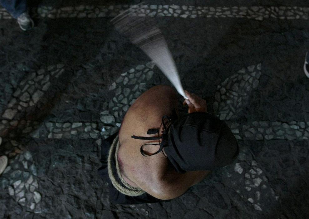 Преклоненный верующий бичует себя во время процессии на улицах мексиканского города Таско, штат Герреро. 9 апреля 2009. Сотни верующих, связанных и бичующих сами себя, прошли по узким мощеным улицам Таско. Этот 500 летний город добытчиков серебра, известен тем, что тут приняты пасхальные ритуалы, которые даже в Мексике – стране глубоко католической, кажутся драматичными и проникновенными. (REUTERS/Henry Romero)