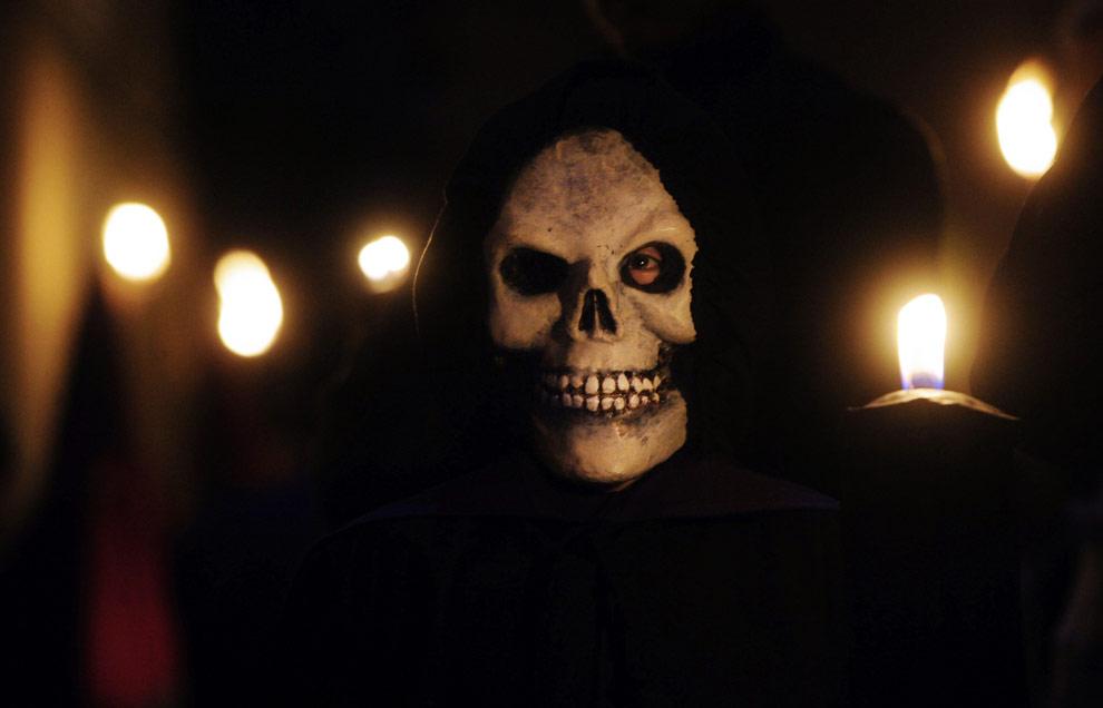 Кающийся грешник в маске танцующего мертвеца во время пасхального шествия в испанском городе Вержес, в пятницу, 10 апреля 2009. (AP Photo/Manu Fernandez)