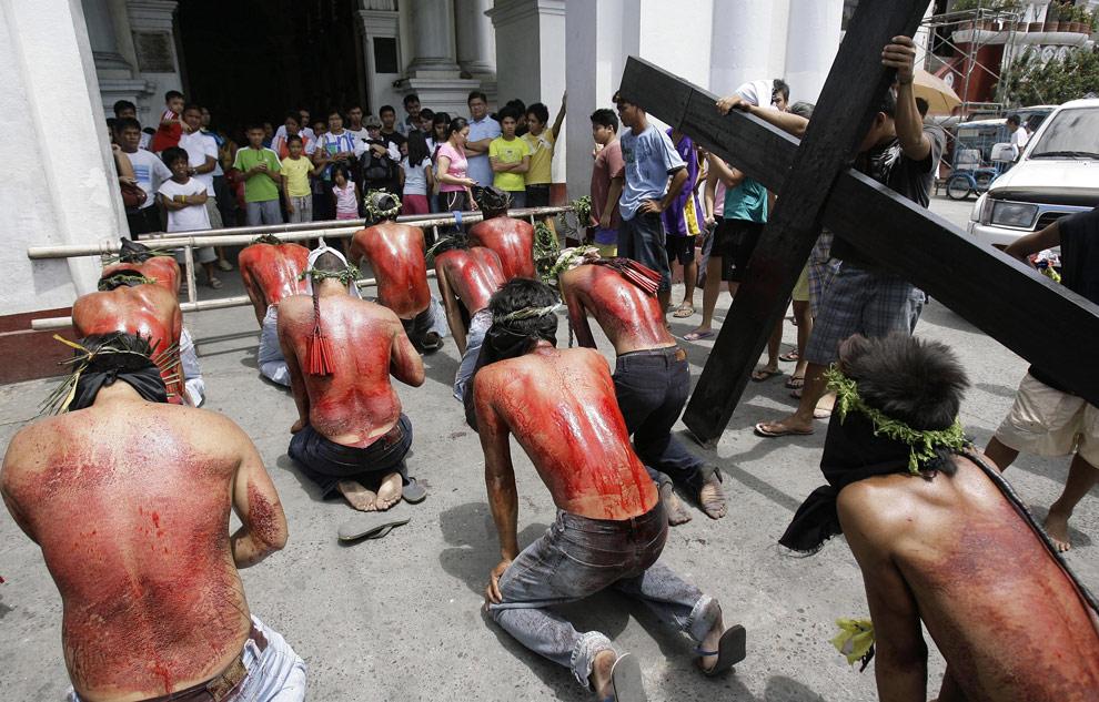 Филиппинские бичующиеся стоят на коленях у входа в церковь, во время обряда искупления грехов в Сан-Фернандо, в провинции Пампанга на севере Филиппин. Страстной четверг, 9 апреля 2009. Церковные лидеры в этой азиатской стране, где большая часть населения исповедует католицизм, с неодобрением относятся к тому факту, что многие филиппинские верующие практикуют самобичевание и покаяние во время страстной недели. (AP Photo/Aaron Favila)