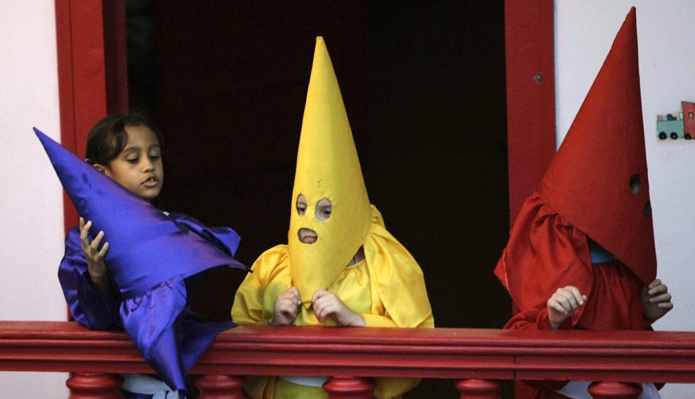 Дети одетые, как кающиеся грешники, готовятся для участия в Шествии факелов в бразильском городе Cidade de Goias, 8 апреля 2009. (REUTERS/Paulo Whitaker)