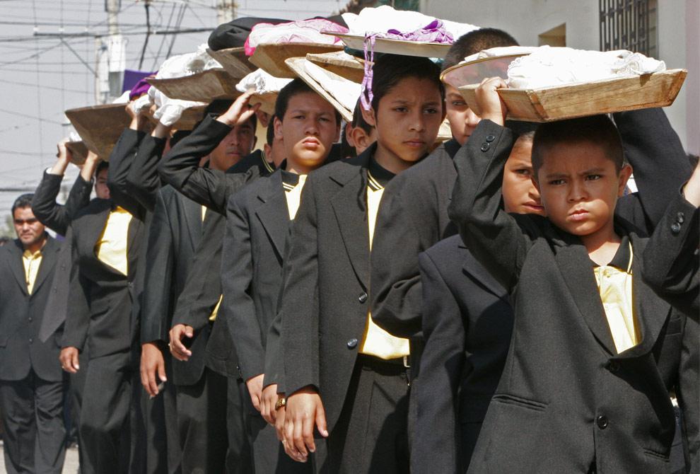 Католики несут корзинки с одеждой, которая изображает одежду Иисуса Христа и которую будут стирать. Празднование Страстной недели в городе Chalchuapa, Сальвадор, в понедельник, 6 апреля 2009. (AP Photo/Luis Romero)