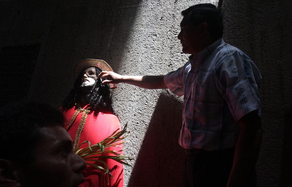 Мужчина касается статуи Иисуса Христа во время празднования Входа Господня в Иерусалим в Манагуа, Никарагуа. Воскресенье, 5 апреля 2009. (AP Photo/ Esteban Felix)