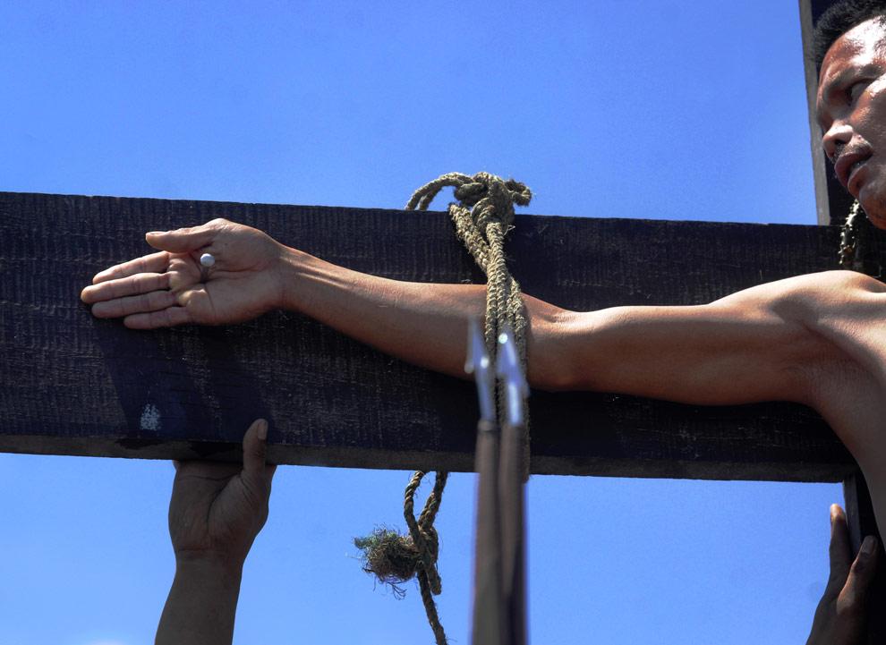 Католический фанатик распятый на кресте во время обряда искупления грехов в Сан-Фернандо, в провинции Пампанга на севере Филиппин. 10 апреля 2009 . Инсценировка «распятия» - популярна среди филиппинцев и осуждается католической церковью. Церемония начинается примерно с 4-х километрового шествия, участники которого несут кресты, повторяя крестный путь Христа. Особо фанатичных участников шествия буквально прибивают к крестам 10-сантиметровыми гвоздями.(JES Аснара/AFP/Getty Images)