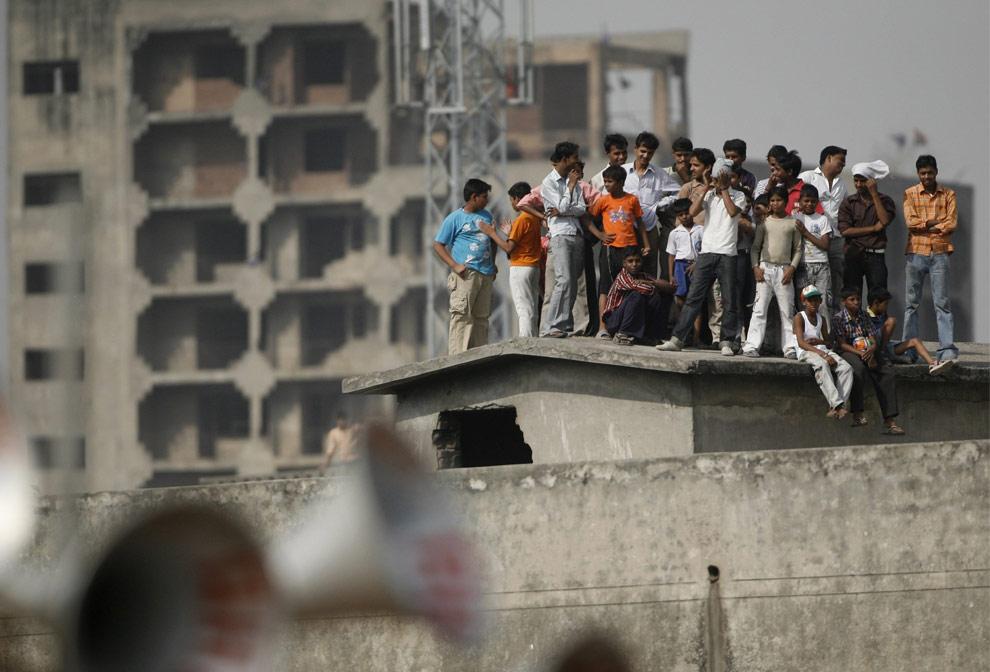 Люди стоят на крыше, в то время как лидер партии Конгресса, Рахуль Ганди (на фото не виден) обращается к народу на митинге в индийском городе Газьабаде (Ghaziabad), в четверг, 30 апреля 2009. (AP Photo/Mustafa Quraishi)