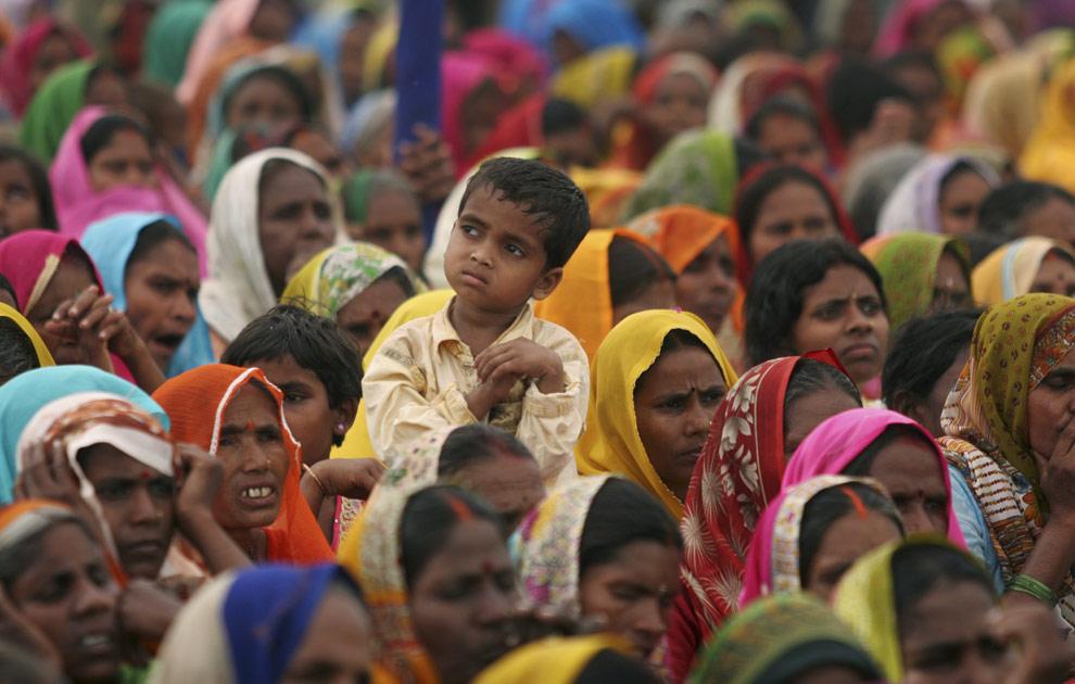 Ребенок выглядывает из толпы сторонников Бахуджан Самадж (Bahujan Samaj), которые слушают выступление лидера партии Майавати (Mayawati) на митинге, посвященном выборам в Аллахабаде 20 апреля 2009. (AP Photo/Rajesh Kumar Singh)