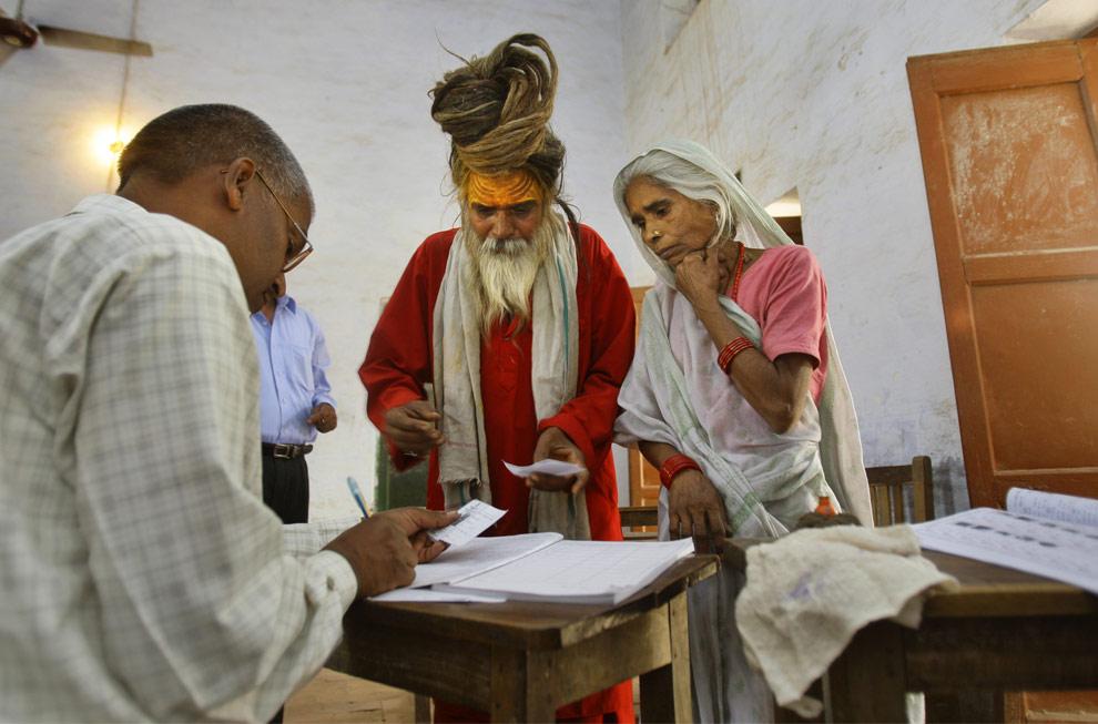 Идуистский праведник, в центре фото, на избирательном участке в Айодхье (Ayodhya), в четверг, 23 апреля 2009. (AP Photo/Gurinder Osan)