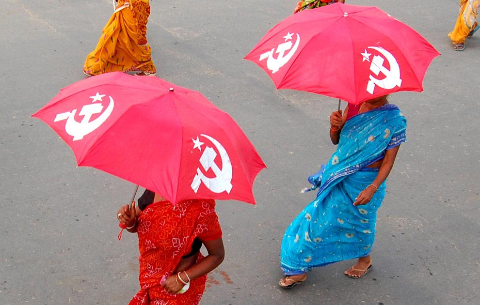 Сторонницы Коммунистической партии Индии (марксистской) несут зонты с серпом и молотом во время митинга посвященного выборам в индийском городе Агартала 21 апреля 2009. (STR/AFP/Getty Images)