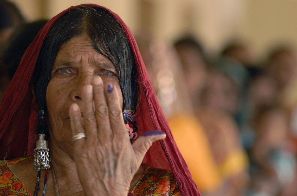 Избирательница показывает свой палец, помеченный чернилами после голосования на избирательном участке в Бапалли (Bapally), к западу от Хайдарабада, 16 апреля 2009. (REUTERS/Krishnendu Halder)