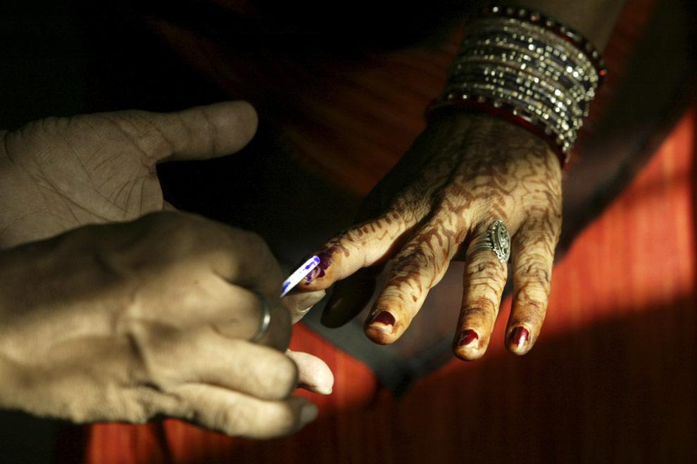 Член избирательной комиссии помечает несмываемыми чернилами палец избирательницы, перед тем, как она пойдет в кабинку для голосования. Индийский город Rae Bareli, четверг, 30 апреля 2009. (AP Photo/Rajesh Kumar Singh)