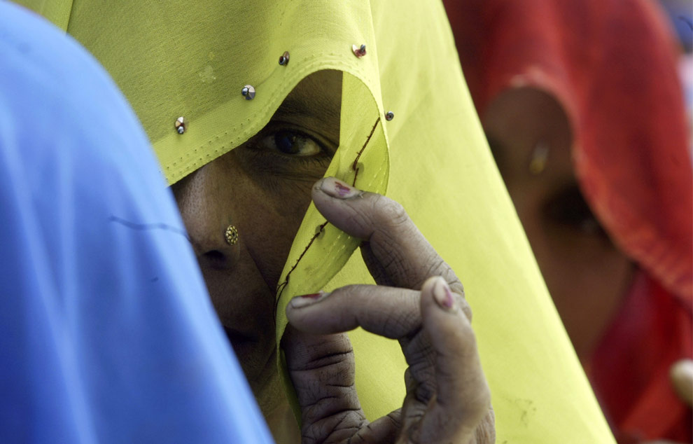 Женщины выглядывают из-под своих платков, стоя в очереди в избирательном участке поселка Jigna в округе Rae Bareli в четверг, 30 апреля 2009. (AP Photo/Rajesh Kumar Singh)