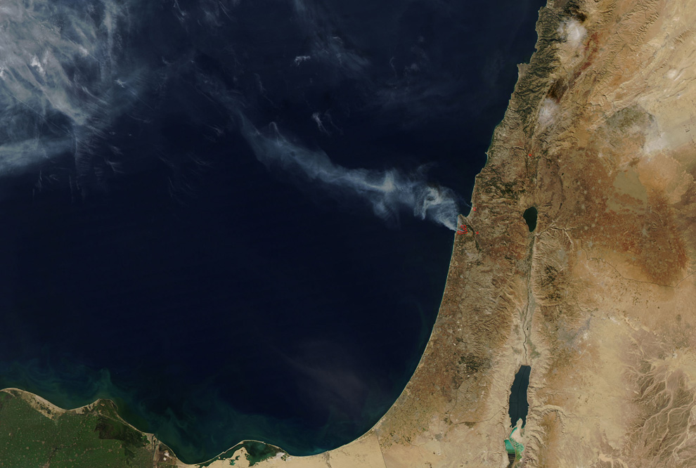 In this satellite image released by NASA, a trail of smoke drifts away from a forest fire outside Haifa, Israel on Friday, Dec. 3, 2010. (AP Photo/NASA) #