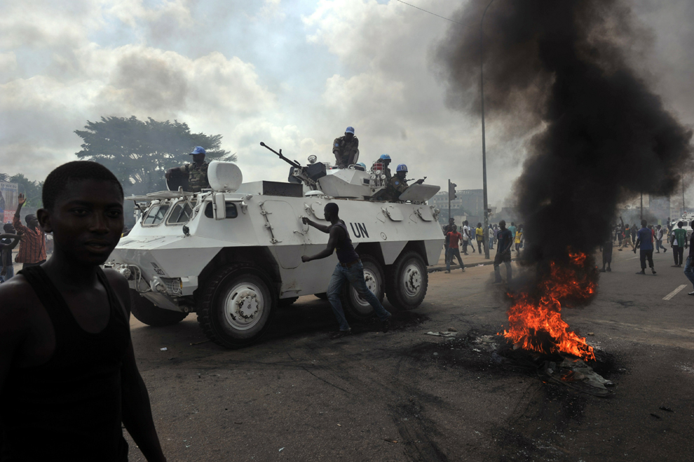"""UN peacekeepers drive past supporters of Alassane Ouattara as they demonstrate and burn tires in the Abobo neighborhood in Abidjan on Feb. 19. The International Crisis Group said, a Belgian watchdog organization, said another civil war in Ivory Coast, involving widespread violence against civilians, is the """"most likely scenario in the coming months."""""""