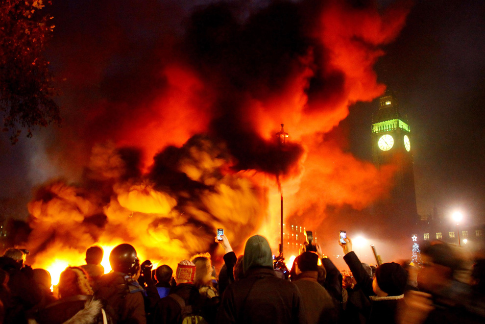 """A fire burns in Parliament Square, Westminster, London, as students demonstrate against planned tuition fee increases on Thursday Dec. 9, 2010. (AP Photo/Gareth Fuller/PA)"""