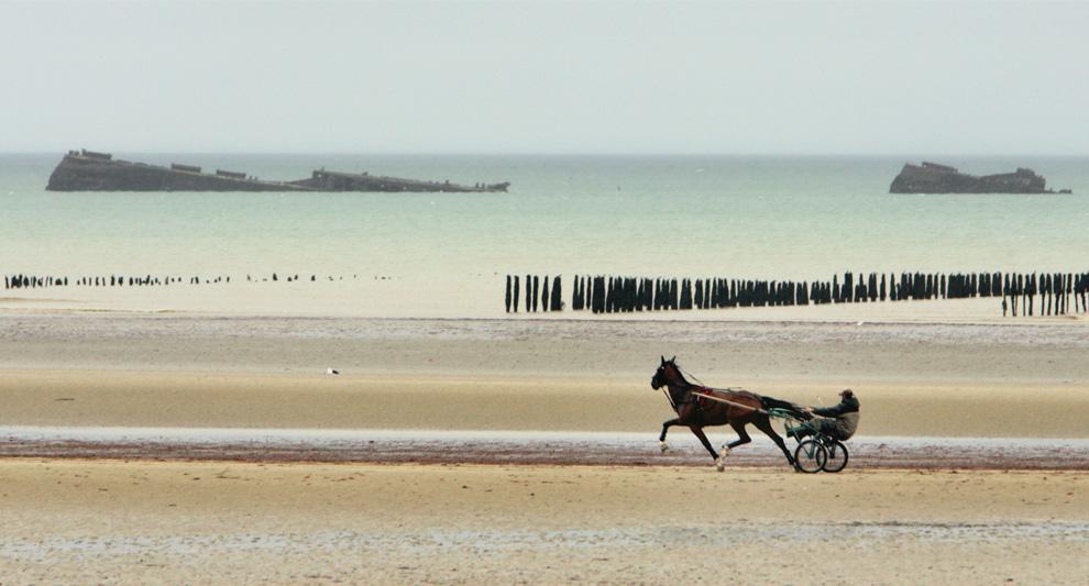 Жокей и его лошадь на пляже Юта Бич. На фоне видны обломки судна времен Второй мировой войны. На этом отрезке берегов Нормандии все еще можно найти следы Второй мировой. (AP Photo/Remy de la Mauviniere)
