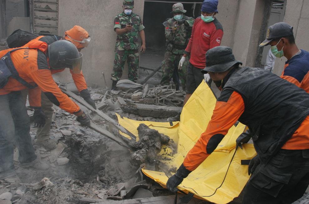Relawan mengankat korban yang tertimbun abu vulkanik