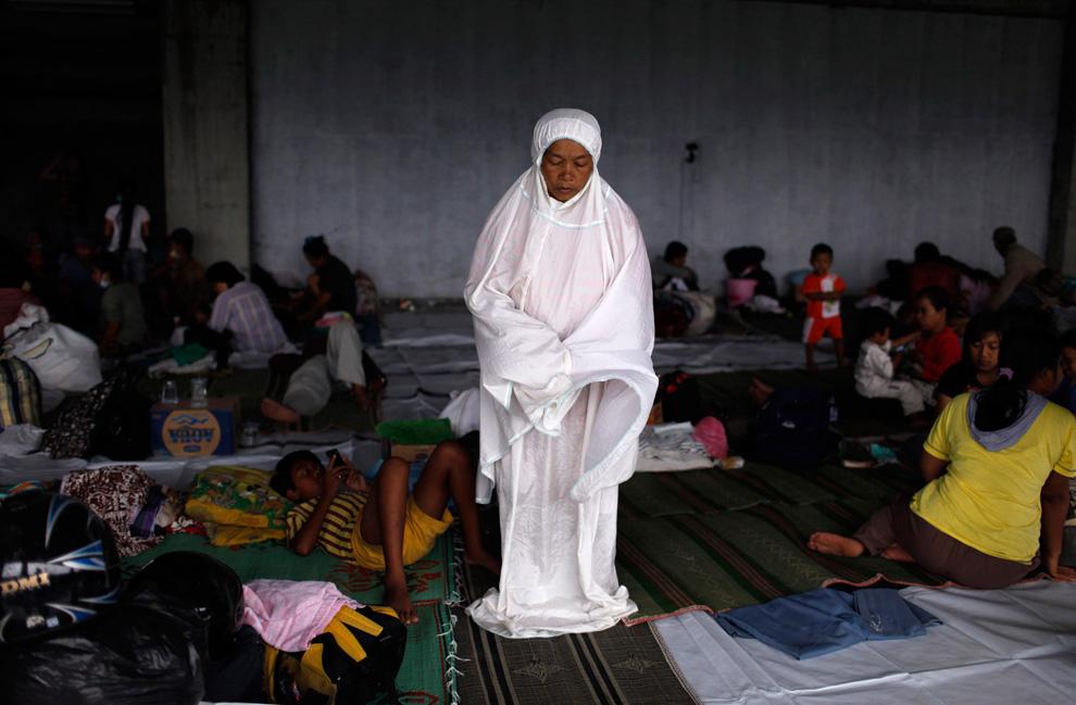 Seorang wanita korban Merapi sedang beibadah